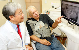 Dr. Choi showing patient a model of teeth