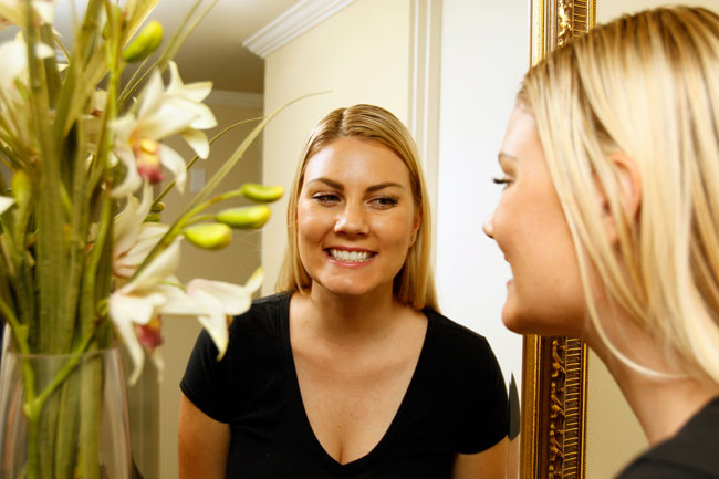 Home with beautiful smile looking in mirror