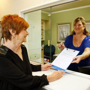 Receptionist giving clipboard to patient