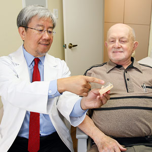 Dr. Choi showing patient a model of implant-supported denture