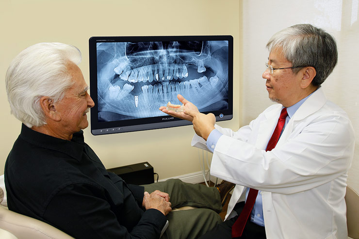 Dr. Choi showing patient teeth model with implants