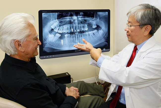 Dr. Choi showing patient an implant model